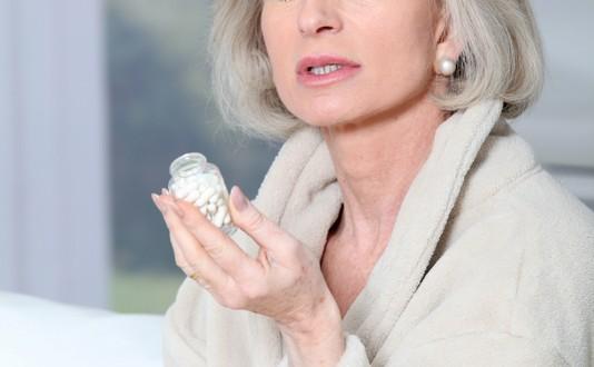Senior woman in bathrobe taking pills